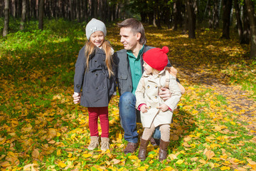 Happy father with his cute daughters in autumn park