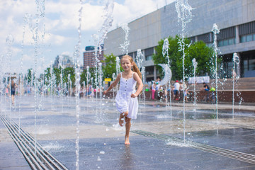 Little cute girl walking in open street fountain at hot sunny