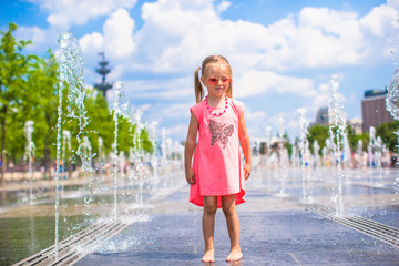 Little happy girl have fun in street fountain at hot sunny day