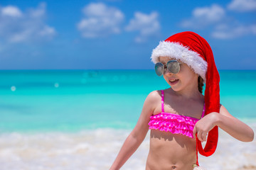 Little cute girl in red Santa hat on tropical beach