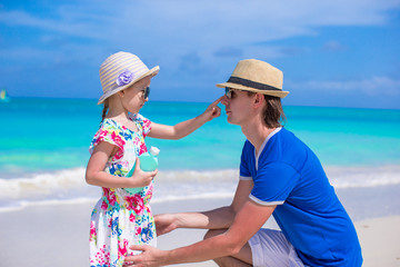 Little girl apply sunscreen on nose of her dad