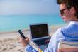 Young businessman using laptop and telephone on tropical beach