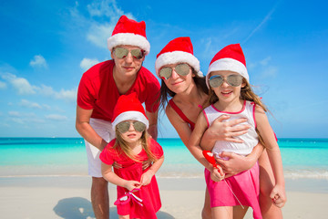 Portrait of happy family in Santa hats on the beach