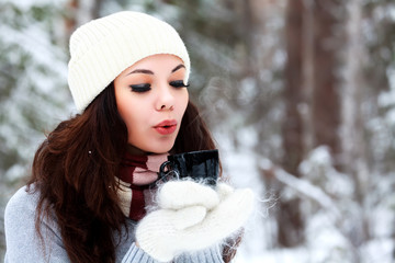 Beautiful young woman in knitted hat and sweater blows on hot te