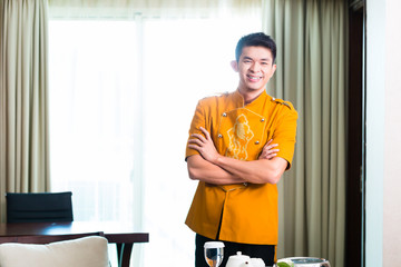 Asian Chinese room service waiter serving food in hotel suite