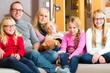 Familie sitzt gemeinsam auf dem Sofa