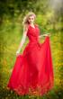 Portrait of young beautiful blonde woman wearing long red dress