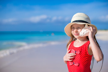 Little cute girl with seashell in hands at tropical beach