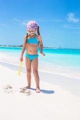 Little girl on seashore during summer vacation