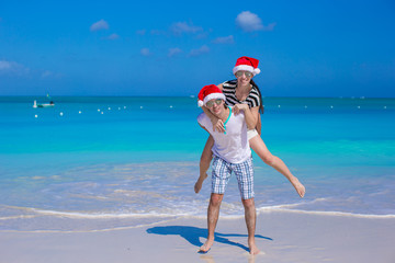 Young happy couple in red Santa hats during their tropical