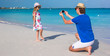 Young father making photo on phone of girl at beach