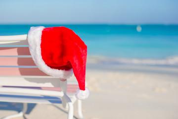 Close up Santa hat on chair longue at tropical beach