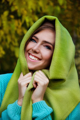 Beautiful young woman covering her head with a blanket
