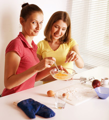two woman friend cooking together