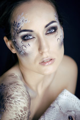 fashion portrait of pretty young woman with creative make up