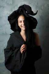 cheerful girl in witch costume smiling
