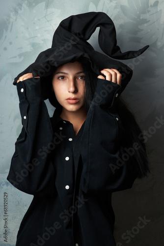 Leinwandbild Motiv girl in a witch costume looks mysteriously