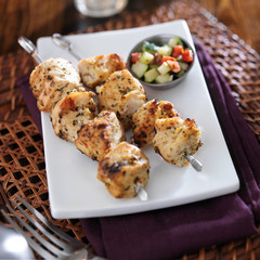 two grilled chicken skewers with cucumber salad
