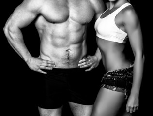 Strong woman and man against a black background