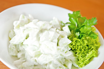 Salad with cucumber and garlic sour cream sauce