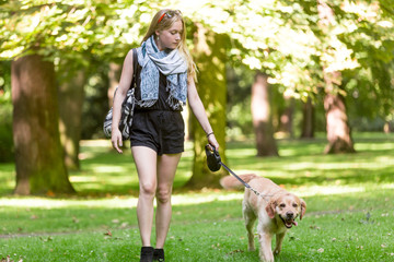 Young woman walking with dog in the park