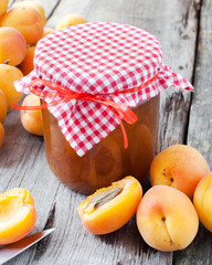 jar of jam and ripe apricot fruits on table