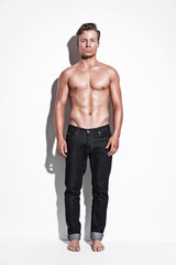 Male fitness model wearing blue jeans. Blonde hair. Against whit