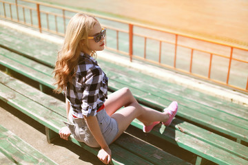 Beautiful young hipster girl sitting on the bench looking away