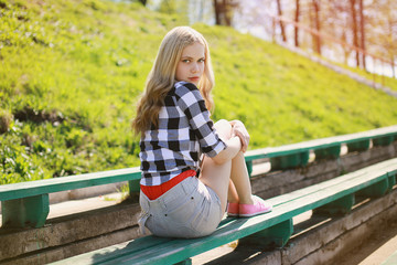 Pretty blonde girl in summer sitting on the bench