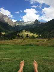 bare feet resting on the grass at the foot of the mountain