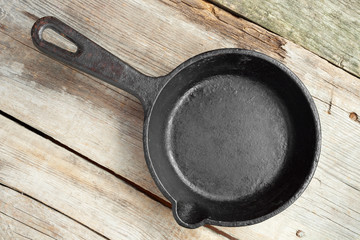 old iron frying pan on wooden rustic table