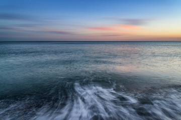 Stunning long exposure seascape image of calm ocean at sunset