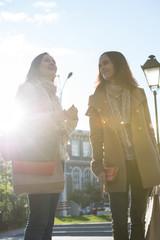 Two women shopping bags walking city