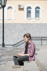 Young bearded hipster student using laptop