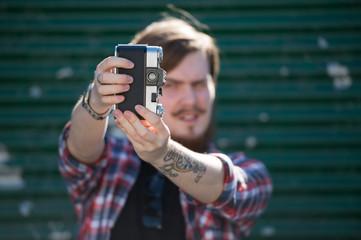 Hipster man making selfie photo retro film camera