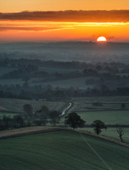 Stunning sunrise over fog layers in countryside landscape