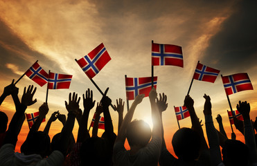Group of People Waving Norwegian Flags in Back Lit