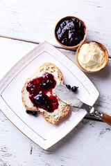 Fresh bread with homemade butter and blackcurrant jam