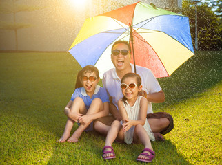 Father and daughters sitting on a meadow with colorful umbrella