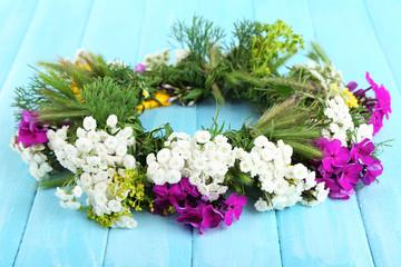 Flower wreath on wooden background