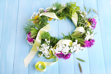 Flower wreath on wooden background