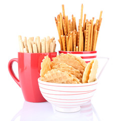 Sticks and biscuits in red cup and white bowl