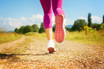 Woman jogging outdoors on sunny summer day
