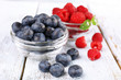 canvas print picture - Glass bowls of raspberries and blueberries on wooden background
