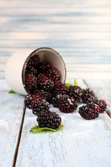 Metal mug of blackberries on wooden table on light background