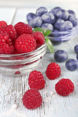 Glass bowls of raspberries and blueberries