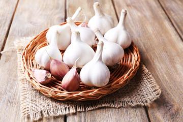 Fresh garlic on wicker mat, on wooden background