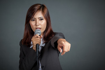 Angry Asian business girl hold a microphone and point
