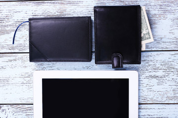 Tablet, wallet with money and notebook on wooden background