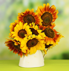 Beautiful sunflowers in pitcher on table on bright background
